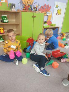 Trzej chłopcy bawią się traktorami i klockami.