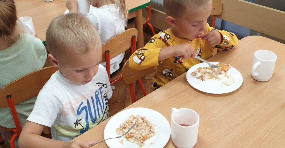 . Olek i Mikołaj ze smakiem jedzą ryż z jabłuszkami.