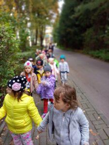 Dzieci spacerują w parach chodnikiem.