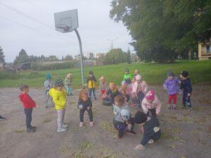 Dzieci zbierają jesienne liście.