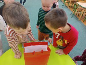 Chłopcy zaglądają do torebki z prezentami.