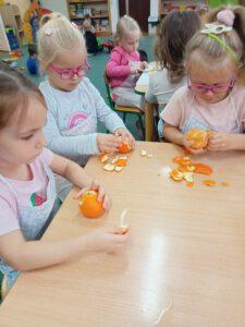 Dziewczynki obierają mandarynki.