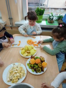 Dziewczynki kroją owoce.
