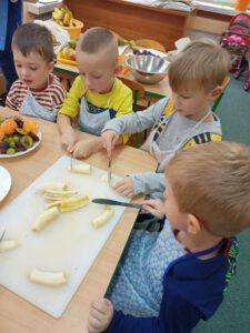 Chłopcy kroją banany.