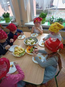 Dzieci jedzą sałatkę.