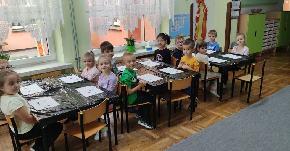 Dzieci przygotowują się do malowania rękami.