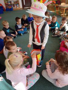 Kacper częstuje dzieci słodyczami.
