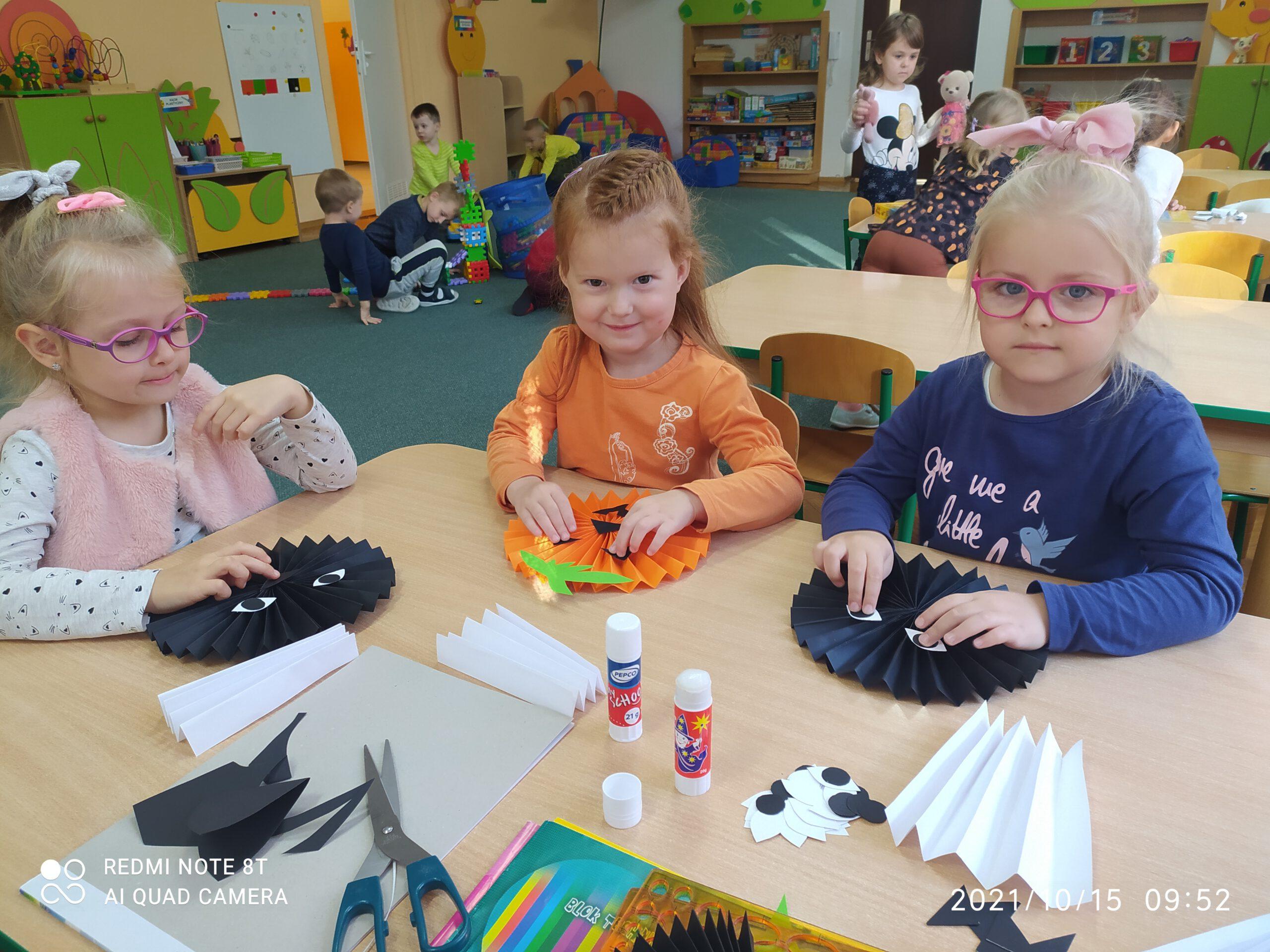 Dziewczynki ozdabiają swoje wachlarze naklejając oczy, nosy, usta, uszy i ręce.